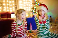 Due sorelle adorabili che celebrano vigilia dei nuovi anni nella stanza a casa meravigliosamente decorata fotografia stock