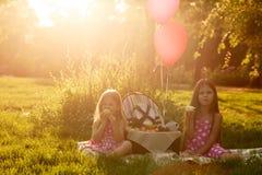 Due sorelle al picnic che mangiano frutta Fotografia Stock