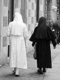Due sorelle anziane con il vestito nero ed il bianco vestono la camminata nella s Immagine Stock