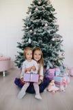 Due sorelle a casa con l'albero di Natale ed i presente Ragazze felici dei bambini con i contenitori e le decorazioni di regalo d Fotografia Stock Libera da Diritti