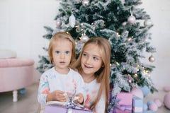 Due sorelle a casa con l'albero di Natale ed i presente Ragazze felici dei bambini con i contenitori e le decorazioni di regalo d Immagini Stock Libere da Diritti