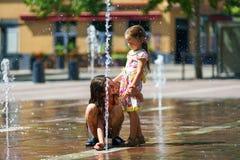 Due sorelle che giocano con la spruzzata della fontana Fotografia Stock