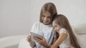 Due sorelle che guardano il PC della compressa, sedendosi sul sofà e giocano, piccoli giovani bambino e sorella dell'adulto archivi video