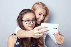 Due sorelle che per mezzo dello Smart Phone per il selfie Fotografia Stock