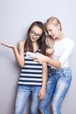 Due sorelle che posano con il telefono cellulare Fotografia Stock Libera da Diritti