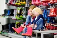 Due sorelle che scelgono e che provano sui nuovi stivali di pioggia Fotografie Stock Libere da Diritti