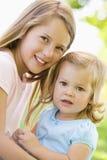 Due sorelle che si siedono all'aperto sorridere Fotografia Stock