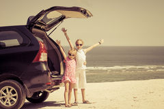Due sorelle che stanno vicino ad un'automobile sulla spiaggia Fotografia Stock Libera da Diritti
