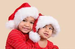 Due sorelle della corsa mixed in cappelli della Santa immagine stock