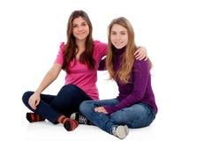 Due sorelle differenti che si siedono sul pavimento Immagini Stock