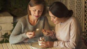 Due sorelle felici che mangiano insieme dessert cremoso dolce, avendo tempo di piacere archivi video