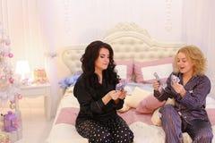 Due sorelle fresche iniziano il viaggio o l'avventura, sedentesi sul letto in b Immagini Stock Libere da Diritti