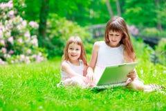 Due sorelle hanno un divertimento con il computer portatile Fotografie Stock