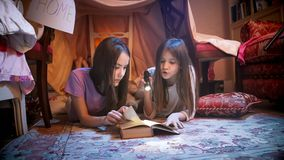 Due sorelle in pigiami che si trovano sul pavimento alla tenda ed al libro di lettura selfmade con la torcia elettrica Fotografie Stock Libere da Diritti