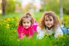 Due sorelle stanno trovando sull'erba verde fresca in primavera fotografia stock