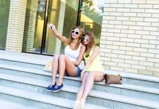 Due sorelle sui punti dell'istituto stanno facendo l'auto, la rete sociale, i vetri e gli shorts del denim Fotografia Stock Libera da Diritti