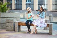 Due sorelle, una bella ragazza castana e una ragazza che camminano nella città, sedentesi su un banco con caffè in mani e Immagini Stock