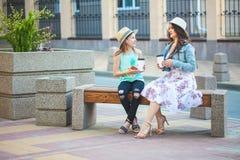 Due sorelle, una bella ragazza castana e una ragazza che camminano nella città, sedentesi su un banco con caffè in mani e Immagini Stock Libere da Diritti
