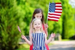 Due sorelline adorabili che tengono le bandiere americane all'aperto il bello giorno di estate Immagine Stock