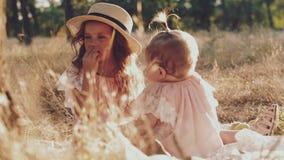 Due sorelline che si siedono sull'erba in natura archivi video