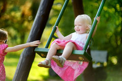 Due sorelline divertendosi su un'oscillazione Immagine Stock Libera da Diritti