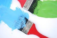 Due spazzole con vernice verde e blu Fotografia Stock