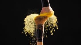 Due spazzole cosmetiche con polvere cosmetica dorata su fondo nero archivi video