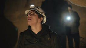 Due speleologi con la torcia elettrica che esplorano la caverna con timore stock footage