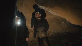 Due speleologi con la torcia elettrica che esplorano la caverna con timore nell'oscurità archivi video