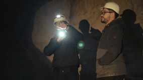 Due speleologi con la torcia elettrica che esplorano la caverna con timore nell'oscurità stock footage