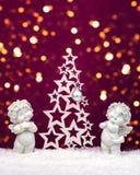 Due statuette di angeli del bambino di Natale su neve con l'albero di Natale fotografia stock