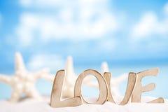 Due stelle marine con il messaggio di amore sulla spiaggia sotto il sole si accendono fotografie stock