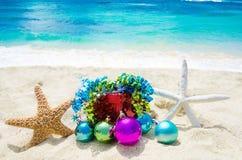 Due stelle marine con le palle di Natale ed il regalo sulla spiaggia - holi Fotografie Stock Libere da Diritti