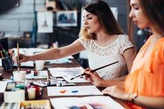 Due studentesse adulte che lavorano alle loro pitture che studiano alla scuola di arte Immagine Stock Libera da Diritti