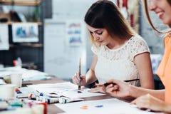 Due studentesse adulte che lavorano alle loro pitture che studiano alla scuola di arte Immagine Stock