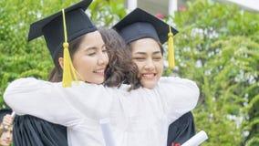 Due studentesse asiatiche con gli abiti ed il cappello di graduazione abbracciano il Th Immagine Stock