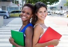 Due studentesse internazionali di nuovo alla parte posteriore Fotografie Stock