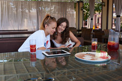 Due studentesse splendide che leggono insieme messaggio di testo sul telefono cellulare mentre sedendosi nella caffetteria, Fotografia Stock