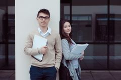 Due studenti attraenti che parlano e che esaminano nella cartella fuori di costruzione la città universitaria Fotografia Stock