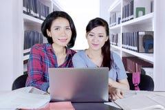 Due studenti che imparano con il computer portatile nella biblioteca Fotografie Stock Libere da Diritti