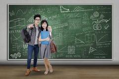 Due studenti che indicano macchina fotografica alla classe Fotografia Stock Libera da Diritti