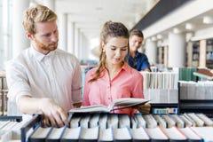 Due studenti che leggono e che studiano nella biblioteca Immagine Stock Libera da Diritti