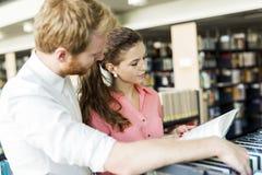 Due studenti che leggono e che studiano nella biblioteca Immagini Stock