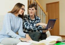 Due studenti che leggono sul sofà Immagini Stock