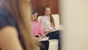 Due studenti che scrivono in taccuini nella classe matrice archivi video