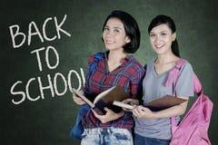 Due studenti che stanno con il testo di nuovo alla scuola Immagine Stock