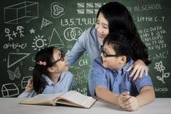 Due studenti che studiano insieme al loro insegnante Fotografia Stock