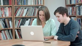 Due studenti che studiano insieme facendo uso del computer portatile immagini stock libere da diritti