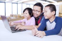 Due studenti che utilizzano computer portatile nella classe con l'insegnante Fotografia Stock