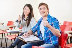 Due studenti con i pollici su Fotografie Stock Libere da Diritti